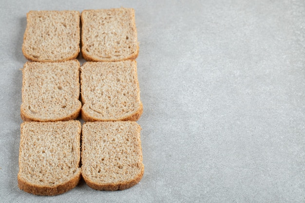 Many of slices of brown bread on a gray background.