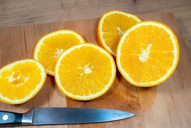 オレンジのスライスが木製のキッチンボードにたくさんあります。新鮮な柑橘系の果物。
