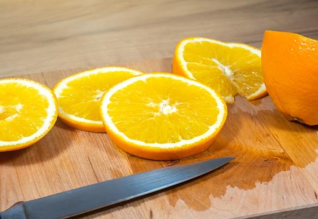 オレンジのスライスの多くは、木製のキッチンボードにあります。新鮮な柑橘系の果物。