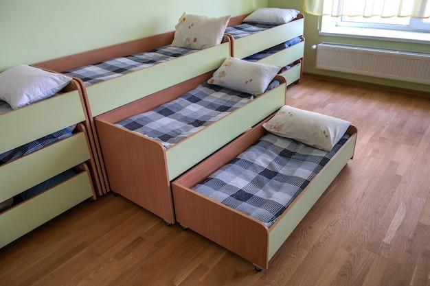 보육 유치원 빈 침실에 많은 작은 침대.