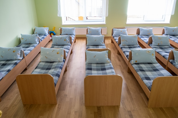 Many small beds with fresh linen in daycare preschool empty bedroom interior for comfortable afternoon nap of the kids.