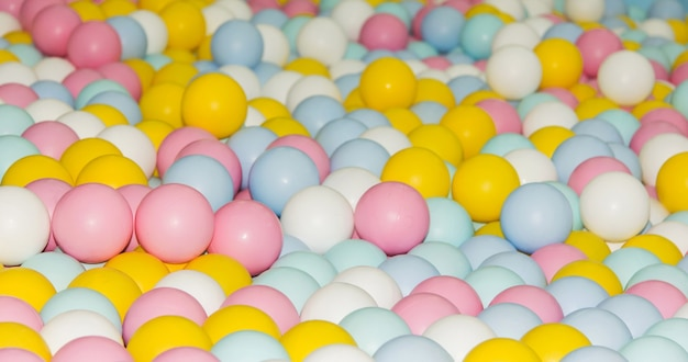 Множество маленьких разноцветных пластиковых мячей в бассейне детская игровая, розовый, желтый, синий, белый
