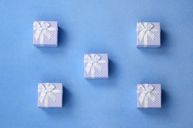 Many small gift boxes in blue color with a small bow lies on a blanket