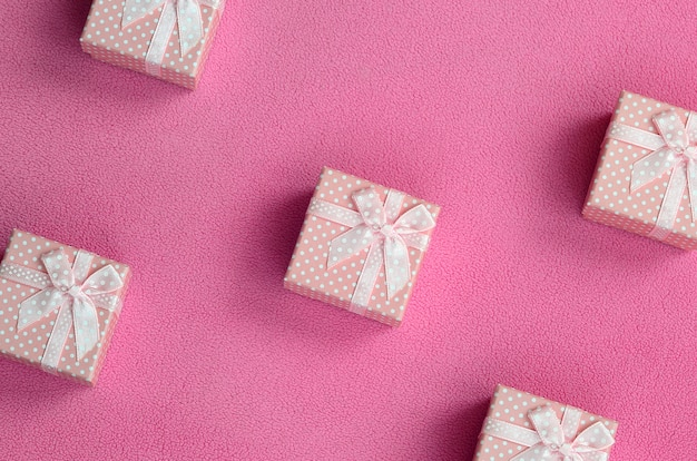 Many small gift boxes in pink color with a small bow