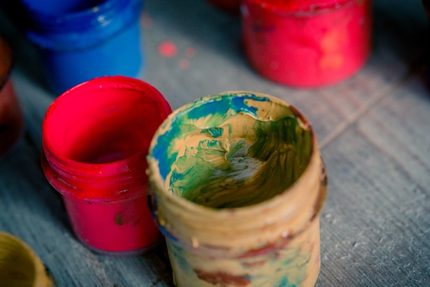 木製の表面にさまざまな色の多くの小さなペンキの瓶