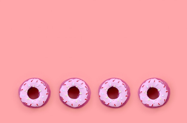 Many small plastic donuts lies on a pastel colorful background