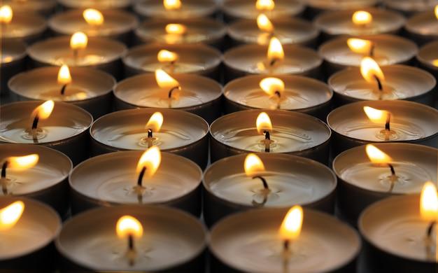 Много небольших круглых горящих свечей, крупный план.