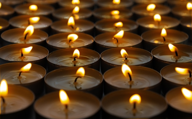 Many small roundness burning candles, close up.