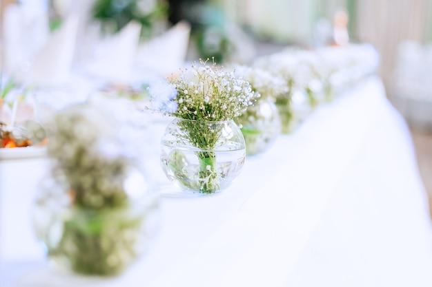 Множество маленьких прозрачных вазочек с водой и букетами гипсофилы на столе свадебного приема