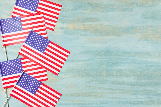 Many small usa flag on blue wooden textured backdrop