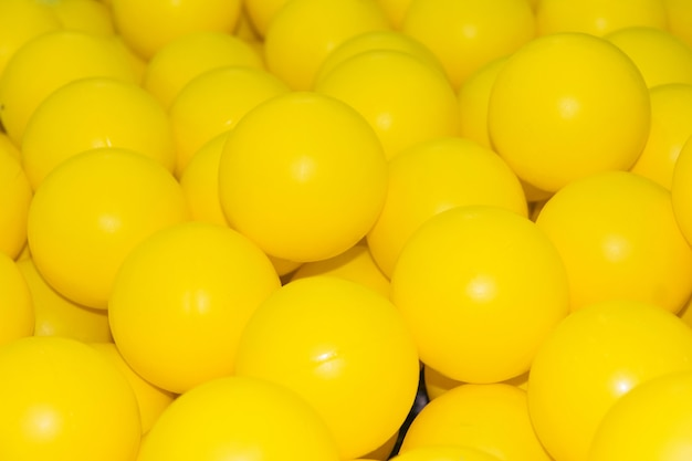 Множество маленьких желтых разноцветных пластиковых мячей в детской игровой комнате цвета бассейна 2021 года.