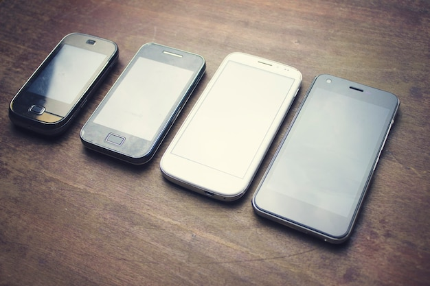 Many smart phones on the wooden table