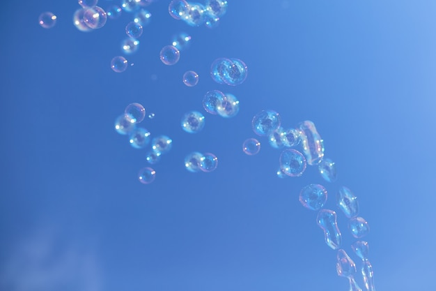 Many soap bubbles against a blue sky