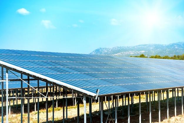 青い空に明るい太陽を当てて、環境にやさしい緑のエネルギーを生み出す多くのソーラーパネル