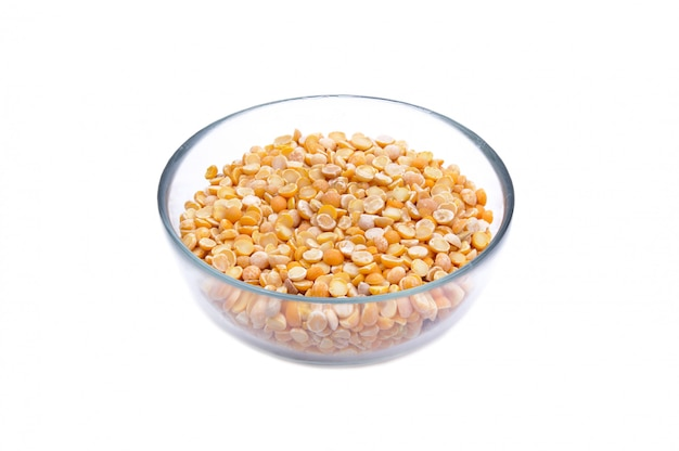 Many split yellow peas grains in glass jar macro close up background