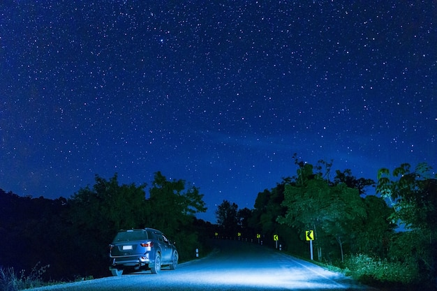 Many star at the night sky with the car on the road