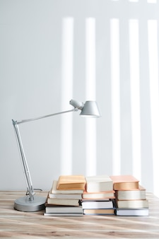 Many students books on big table with modern lamp