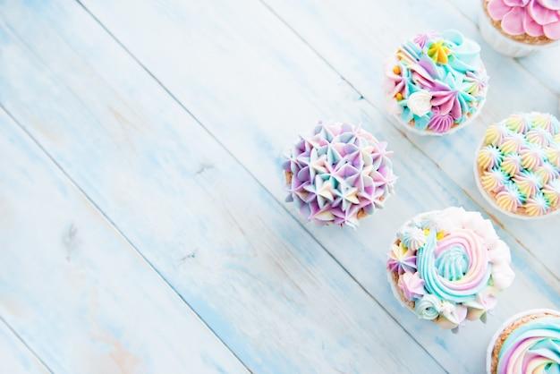 꽃과 버터 크림과 함께 많은 달콤한 생일 컵 케이크