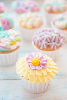 꽃과 버터 크림으로 많은 달콤한 생일 컵 케이크
