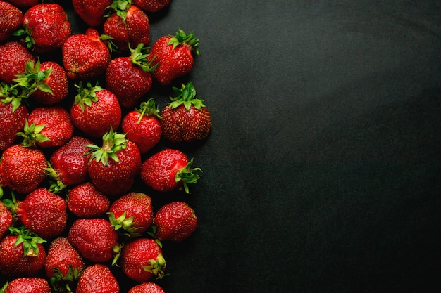Many sweet strawberries lies on a black background