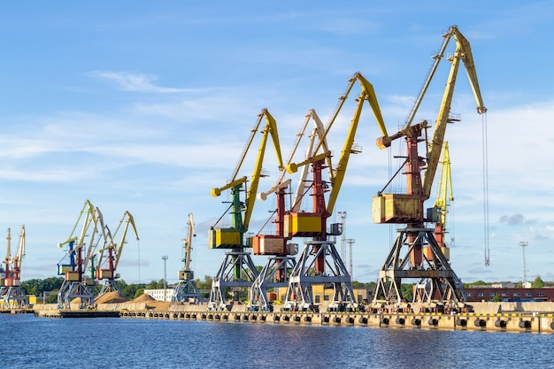 Many tall cargo cranes stand on the banks of the venta river.