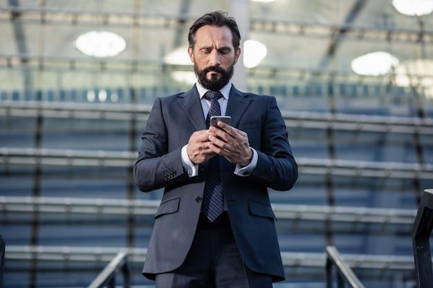 多くのタスク。メッセージを書いている間電話を持っている深刻なひげを生やしたビジネスマンの腰