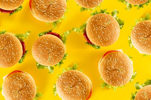 Many tasty fresh unhealthy hamburgers with ketchup and vegetables on yellow vibrant bright background. top view with copy space.
