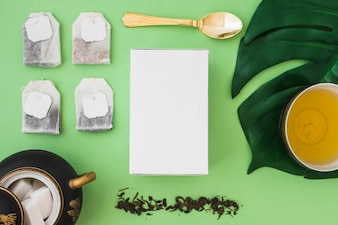 Many tea bag with sugar cubes and box on green background