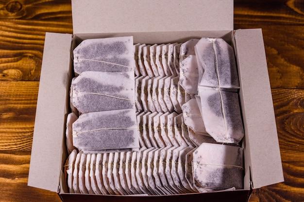 素朴な木製のテーブルの上の箱にたくさんのティーバッグ