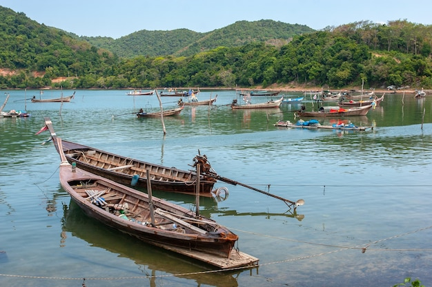 Many tethered long fishing boats with long propellers in the bay