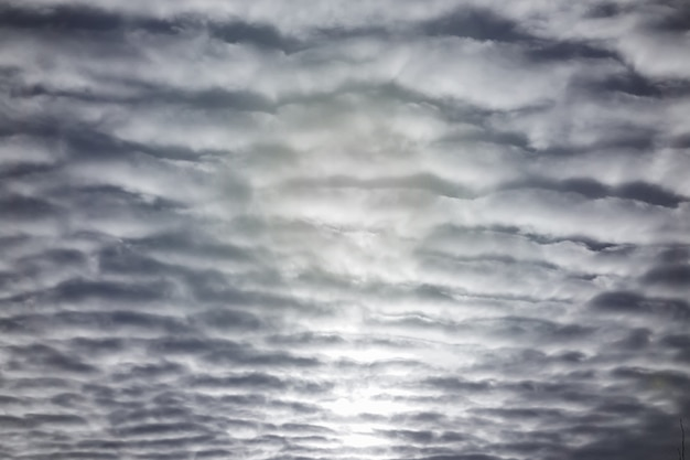 Many textured clouds in the blue sky with sunlight