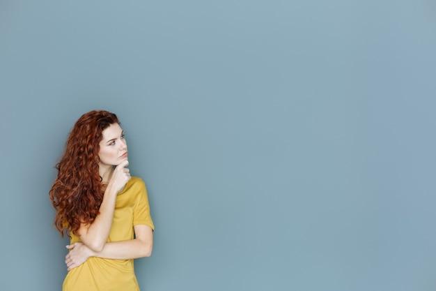 多くの考え。あごを持って、考えに集中しながら脇を見る真面目で魅力的な思いやりのある女性