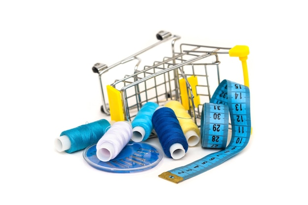 Many threads lie in the cart on a white background with a rubber ruler and needles.