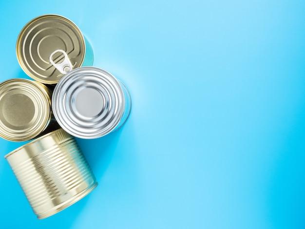 Многие жестяные банки золотого и серебряного цвета, изолированные на синем фоне, вид сверху, копия пространства, макет. концепция: предметы первой необходимости, пожертвования на период карантина по коронавирусу.