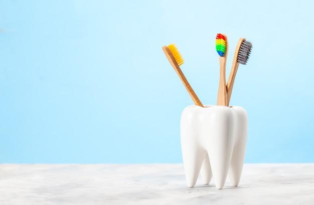 Многие зубные щетки в стакане в форме зуба. синий фон. понятие о том, как правильно выбрать зубную щетку.