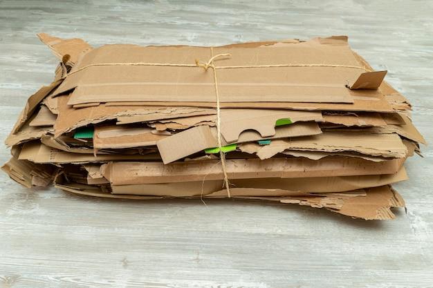 많은 찢어진 판지 상자가 번들로 조립되어 재활용을 위해 쌓입니다.