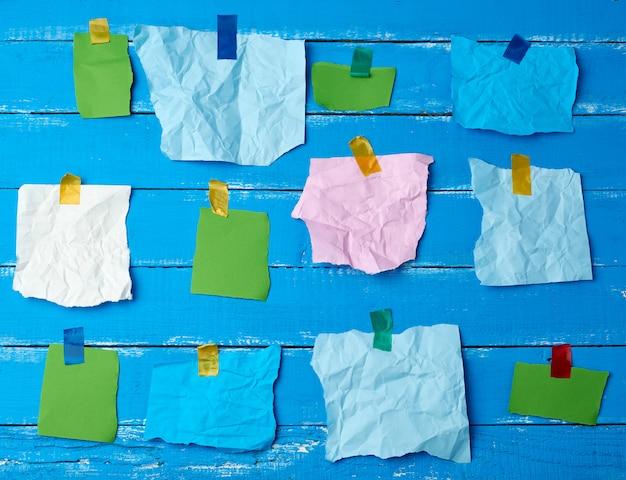 Много разорванных разноцветных кусочков бумаги, склеенных скотчем на синей деревянной поверхности