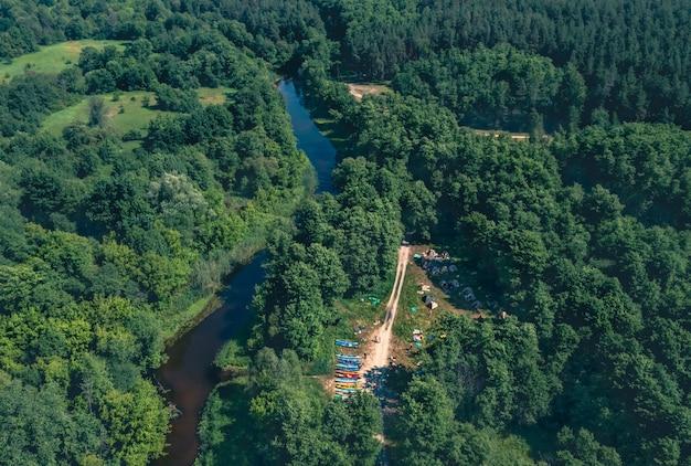 Много туристических байдарок на берегу реки на опушке леса