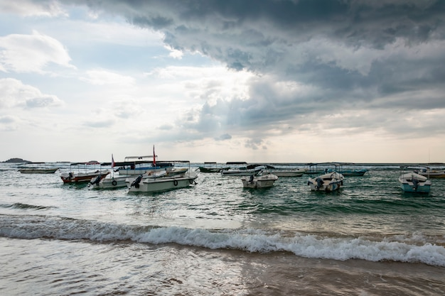 Many traditional boats and yachts by the sea or ocean. an impending tropical storm with rain and dark rain clouds in the sky and the sun breaking through them