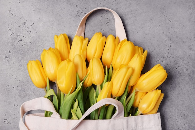 회색 표면에 노란색 꽃잎이있는 많은 튤립, 꽃의 꽃다발