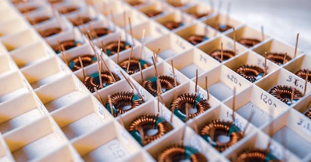 多くのねじれた銅コイルは、電子機器のさらなる生産のためにコンパートメントにあります。医療機器の生産のための工場コンセプト
