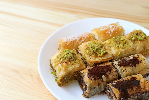 Many types of baklava pastries on white plate served on wooden table