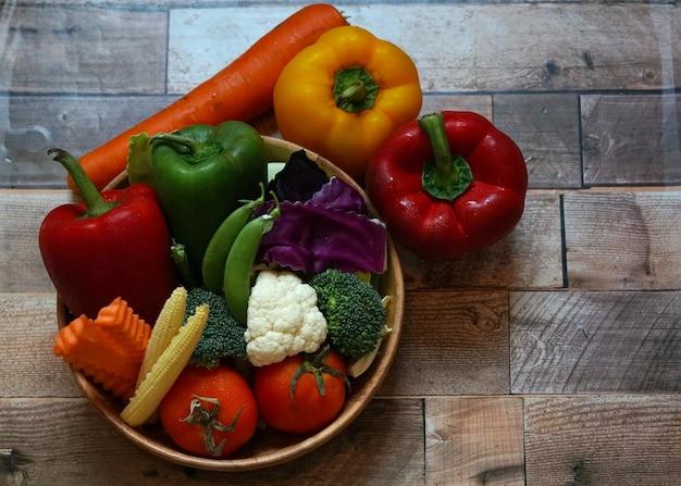 많은 종류의 야채가 빨간색과 노란색 피망과 같은 나무 배경에 있는 그릇에 있습니다