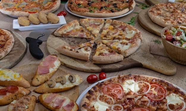 Many types of tasty pizzas on wooden background.copy space