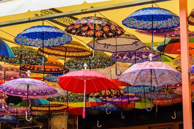 Многие зонтики свисают с потолка в уличном кафе