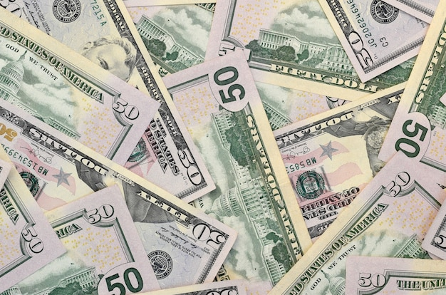 Many us fifty dollar bills on flat background surface close up. flat lay top view. abstract business concept