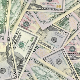 Many us fifty dollar bills on flat background surface close up