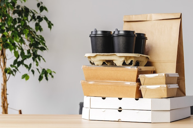 Many various take-out food containers, pizza box, coffee cups and paper bags on light grey background. food delivery