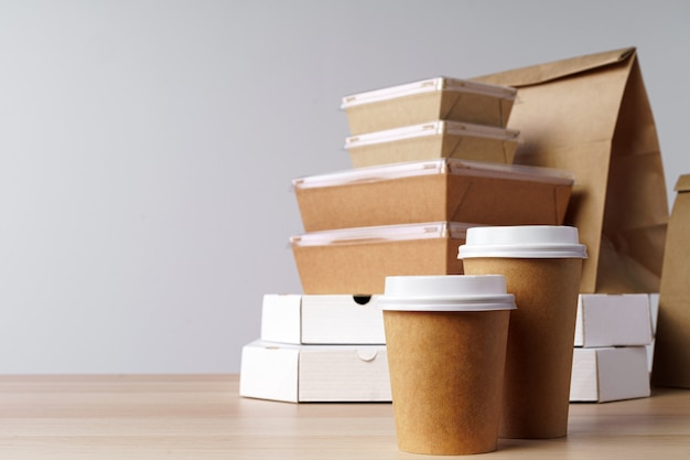 Many various take-out food containers, pizza box, coffee cups and paper bags on light grey