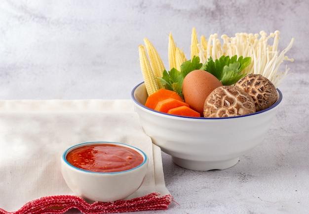 흰 그릇에 담긴 많은 야채에는 당근, 아기 옥수수, 표고 버섯, 황금 바늘, 셀러리 및 닭고기 달걀이 포함됩니다. 스키야키 세트와 소스.